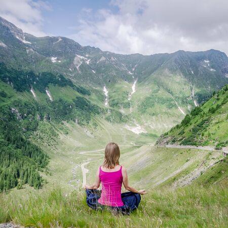 position d amour: Jeune femme méditer sur le sommet de la montagne