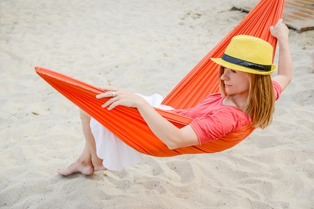 Woman relaxing on red hammock at the beach