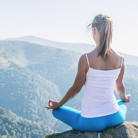 position d amour: Young woman meditate on the top of mountain Banque d'images