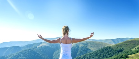 Young woman meditate on the top of mountain Archivio Fotografico