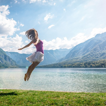 Girl jumping on the lake Stock Photo