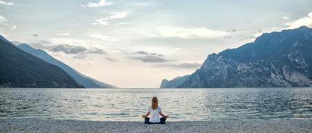 Frau am See meditiert Standard-Bild - 71051143