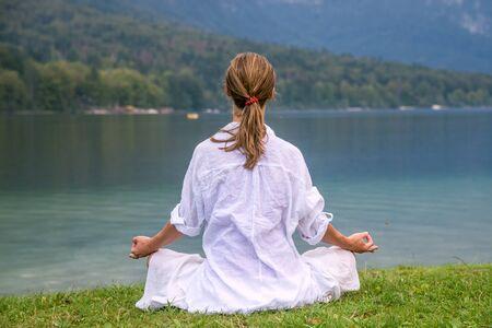 composure: Woman meditating at the lake