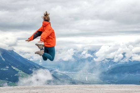 mujer mirando el horizonte: joven saltando en la cima de la montaña Foto de archivo