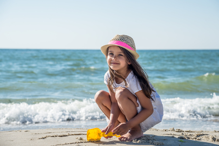 Happy little girl playing on the beach Stock Photo