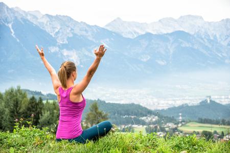 mujer mirando el horizonte: joven meditar mujer encima de la montaña Foto de archivo