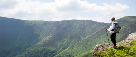 Jonge vrouw die in de bergen wandelt Stockfoto