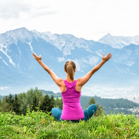young woman on top of the mountain meditate Stock Photo