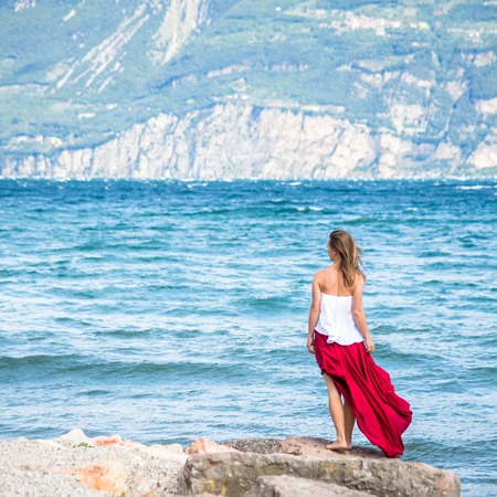chic: Beautiful girl in red dress staying by the sea. Stock Photo
