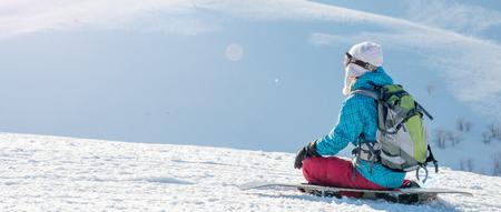 丘の斜面の上に座ってスノーボードを持つ若い女性