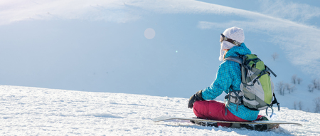 Young woman with snowboard sitting on the slope of hill Stok Fotoğraf