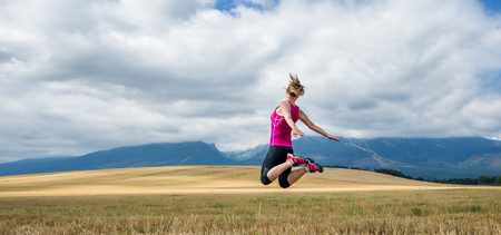 Young woman jumping in the mountains Stock Photo