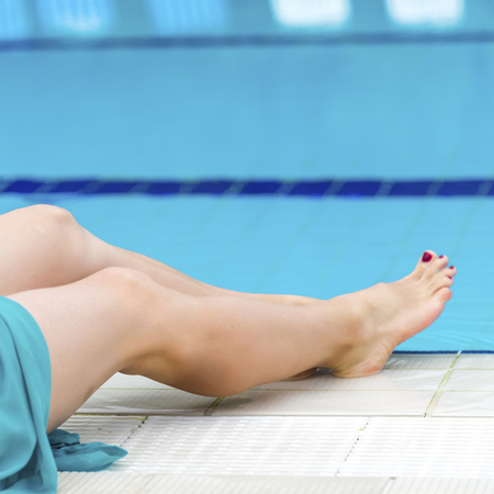 Woman legs in a swimming pool. Stock Photo