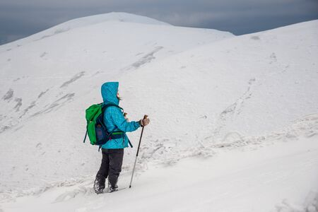 Young woman hiking in the snow mountains Reklamní fotografie
