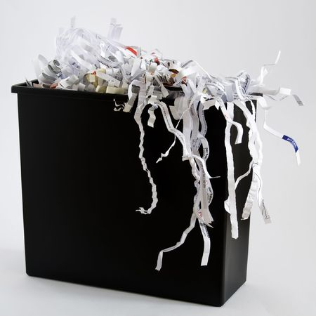 A wastebasket filled with shredded paper.