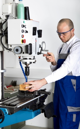 cutting machine is: worker with safety glasses at milling machine Stock Photo