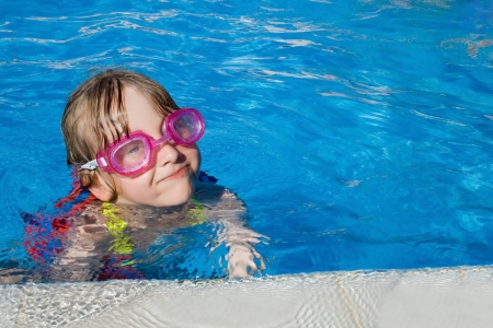 Little girl swimming in pool with goggles