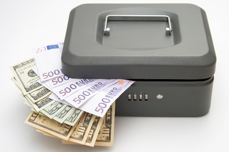 Closed cashbox and money on white background