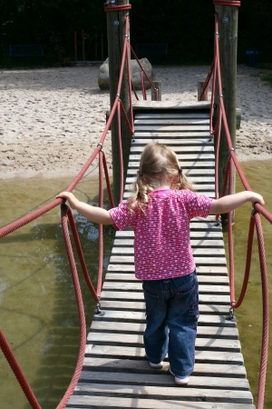 little girl walking on a suspended wooden bridge back view Stock Photo