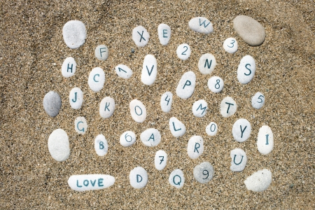 stones on a sand background, numbers and letters