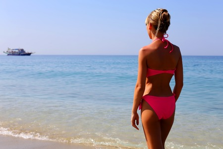 Woman in pink bikini standing on the beach and looking at the sea Stock Photo