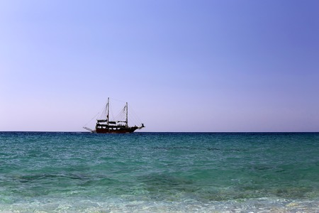 single pirate sailing ship at open sea under clear sky