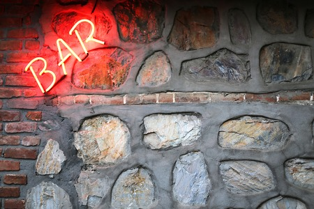 Bar sign on a stone wall background