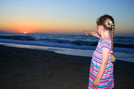 little girl standing on the beach and looking at sunset