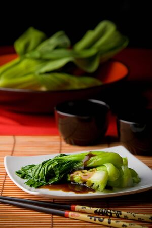epicurean: Dish of steamed bok choy with oyster sauce on white plate amid Asian style table setting Stock Photo