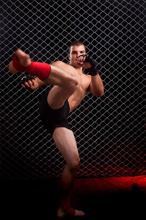 Mixed martial artist posed in front of chain link photo