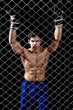 Mixed martial artist posed behind chain link Reklamní fotografie
