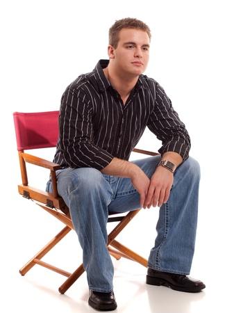 カジュアルな若い男の取締役の椅子に座っています。