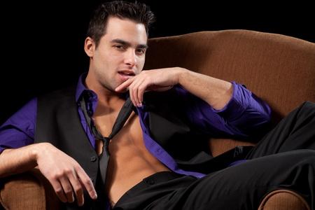 shirt unbuttoned: Uomo su sedia Archivio Fotografico