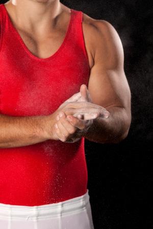 Young adult male gymnast  Studio shot over black