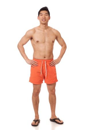 boardshorts: Young man in swimwear. Studio shot over white.