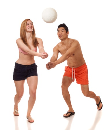 board shorts: Young couple playing volleyball. Studio shot over white.