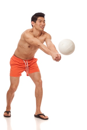 boardshorts: Young man playing volleyball. Studio shot over white.