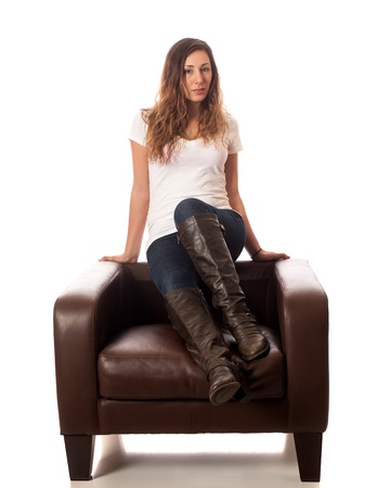 Casual young woman on leather chair. Studio shot over white. photo