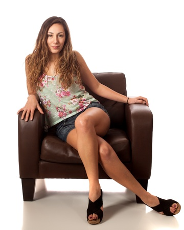Casual young woman on leather chair. Studio shot over white.