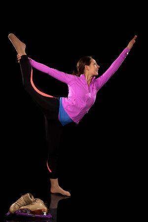Figure skater stretching  Studio shot over black  Banco de Imagens