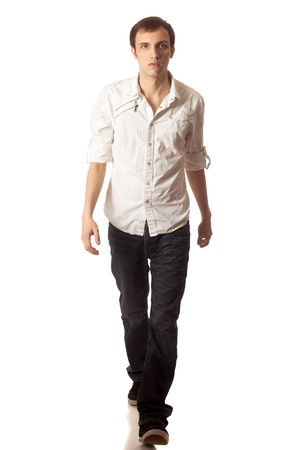 Casual young man walking. Studio shot over white. photo