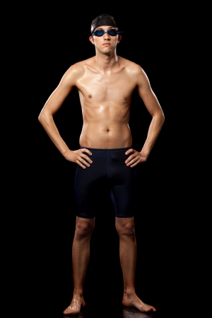 Young adult male swimmer. Studio shot over black. photo