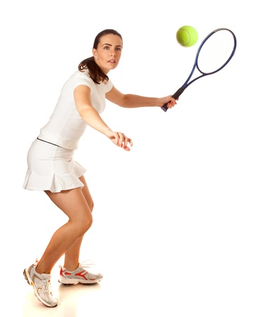 forehand: Adult woman playing tennis. Studio shot over white.