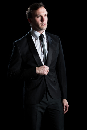 young adult man: Young adult man in a black suit and tie. Studio shot over black.