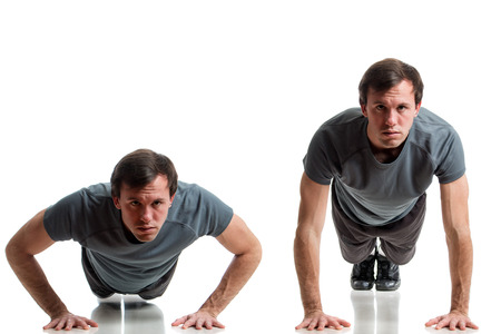 push: Young adult man doing push ups. Studio shot over white.