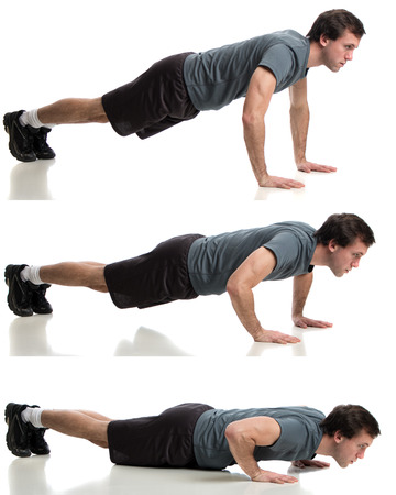 Young adult man doing push ups. Studio shot over white. photo
