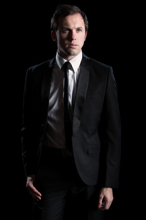 Young adult man in a black suit and tie. Studio shot over black.