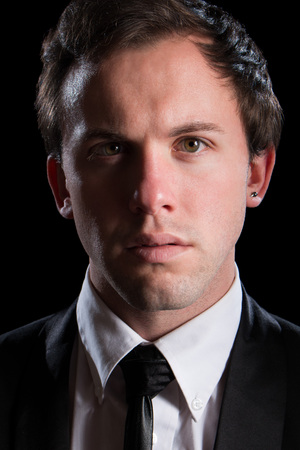 Head shot of a well dressed man. Studio shot over black.