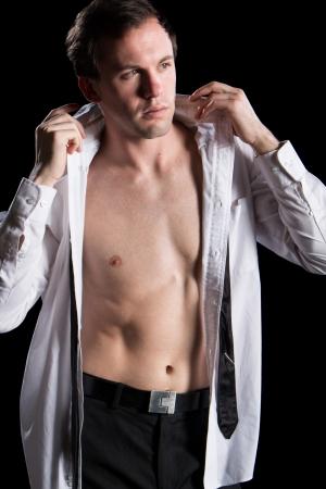 Attractive man with shirt open. Studio shot over black. photo