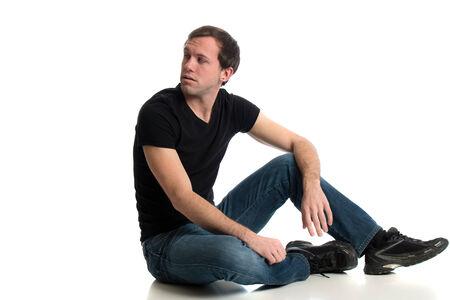 hombre sentado: Hombre joven en pantalones vaqueros y una camiseta de color negro. Estudio tirado sobre blanco. Foto de archivo